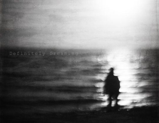 black and white dream like image of a blurred figure by the sea